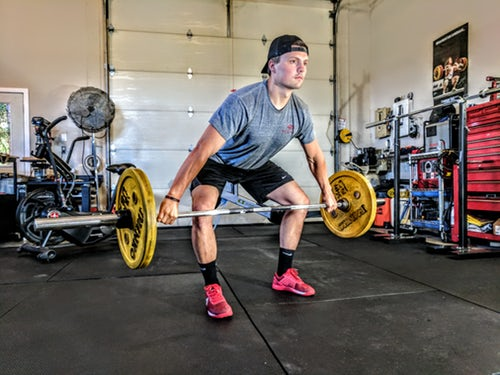 Man dead lifting with equipment used for fitness